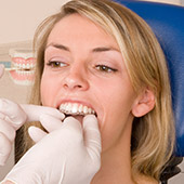 Dentist placing Invisalign tray in Garland