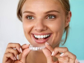 woman smiling holding a clear aligner