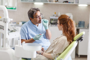 Dentist talking to patient in dental chair