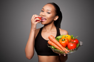 fit woman smiling eating vegetables