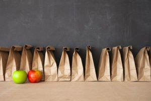 a line of brown paper sack lunches and two apples