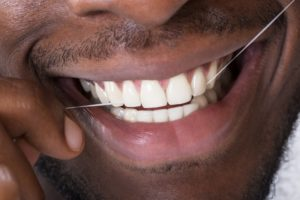 Smiling man flossing his teeth