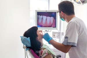 Dentist checks mouth for oral cancer